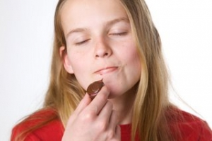 Girl savors the moment as she eats chocolate