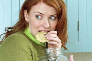 Woman secretly eating cookies